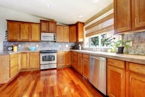 Kitchen interior with lots of wood, stainless steal appliances and wood floors